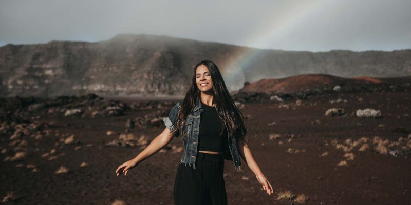 smiling woman with a rainbow behind her
