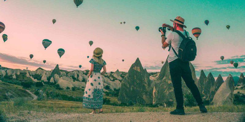 woman looking at hot air ballons while man takes photo