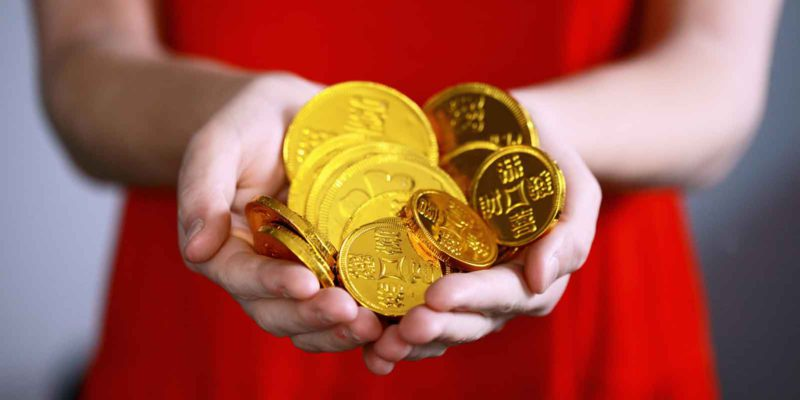 woman in red holding Chinese golden coins