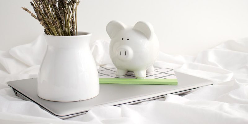 white piggy bank and vase on top of a notebook and laptop