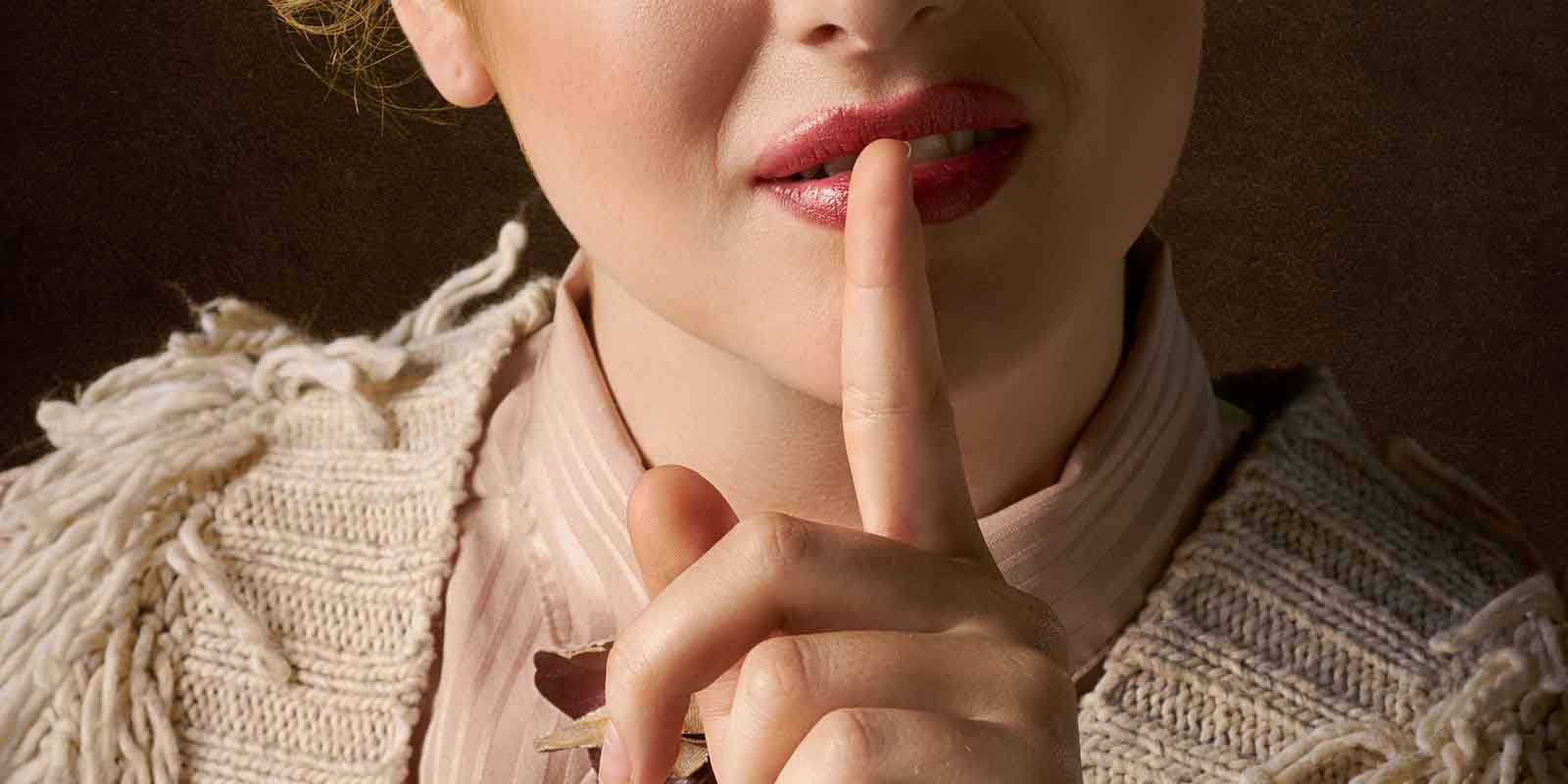 woman with fingers on her lips in a classic shush position