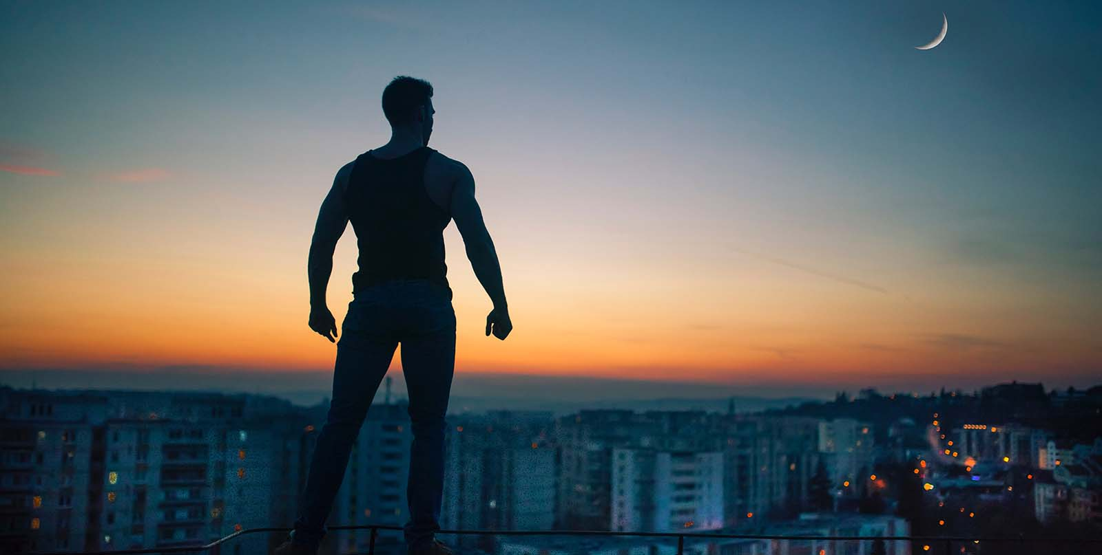 silhouette photo of man standing on peak front of high-rise buildings
