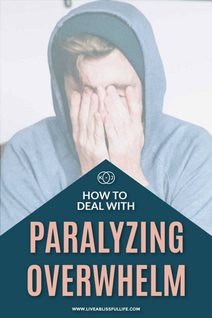 text: how to deal with paralyzing overwhelm image: man in blue sweater covering his face with both hands