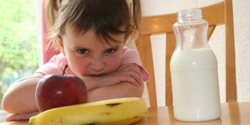 How To Teach A Child To Eat Healthy - unhappy young girl with an apple, banana and milk