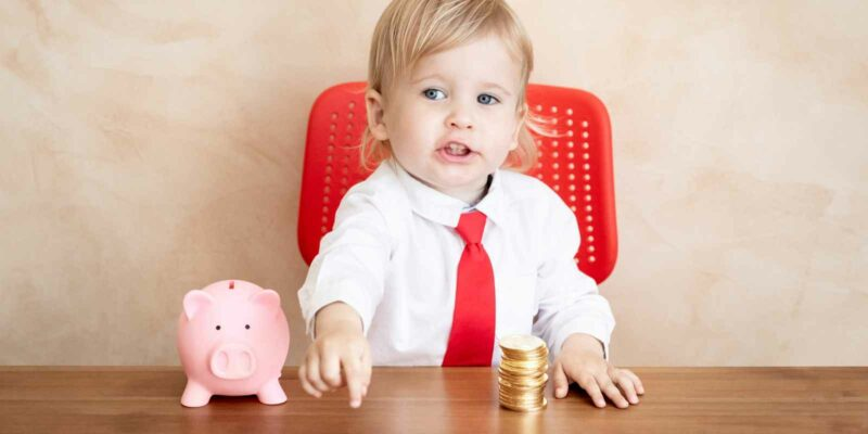 toddler with piggy bank and a pile of coins