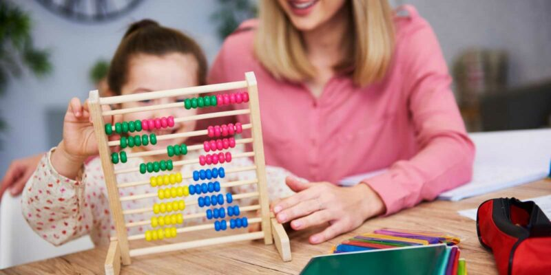 woman and young girl playing with a colourful abacus