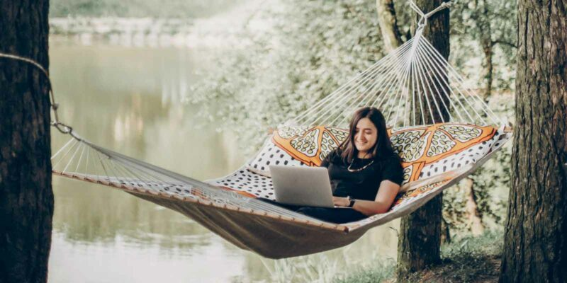 is working remotely right for me - woman working on laptop on a hammock