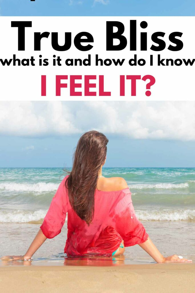 Text: True bliss. What is it and how do I know I feel it? Image: Woman in bright pink top and a blue bottom bikini sitting on the sand looking out at the sea.
