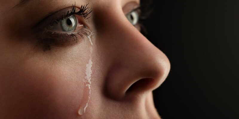 blue-eyed woman with tears on her face