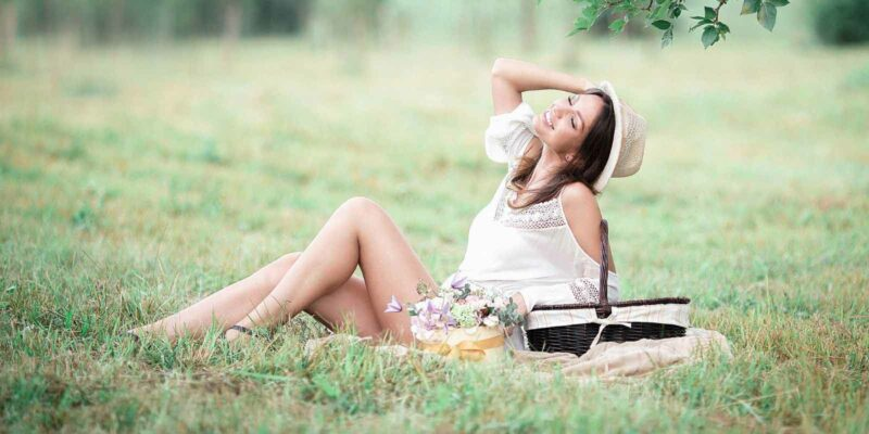 pretty woman sitting on a field with a posy of flowers and feeling blissful